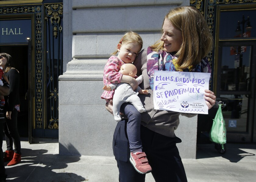 Kim Turner holds her daughter, Adelaide, before a rally in support of paid family leave at San Francisco City Hall on Tuesday.