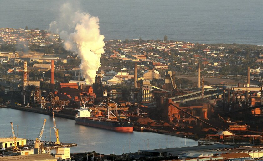 FILE - In this July 2, 2014 file photo, smoke billows out of a chiming chimney stack of BHP steel works at Port Kembla, south of Sydney, Australia. BHP Billiton, the world's biggest miner, reported an 86 percent drop in annual profit on Tuesday, Aug. 25,2015, amid plummeting commodity prices, as the company warned that China's slowing economy would lead to further market volatility. BHP saw a net profit of $1.9 billion for the 12 months to June 30, down from $13.8 billion a year ago.(AP Photo/Rob Griffith, File)