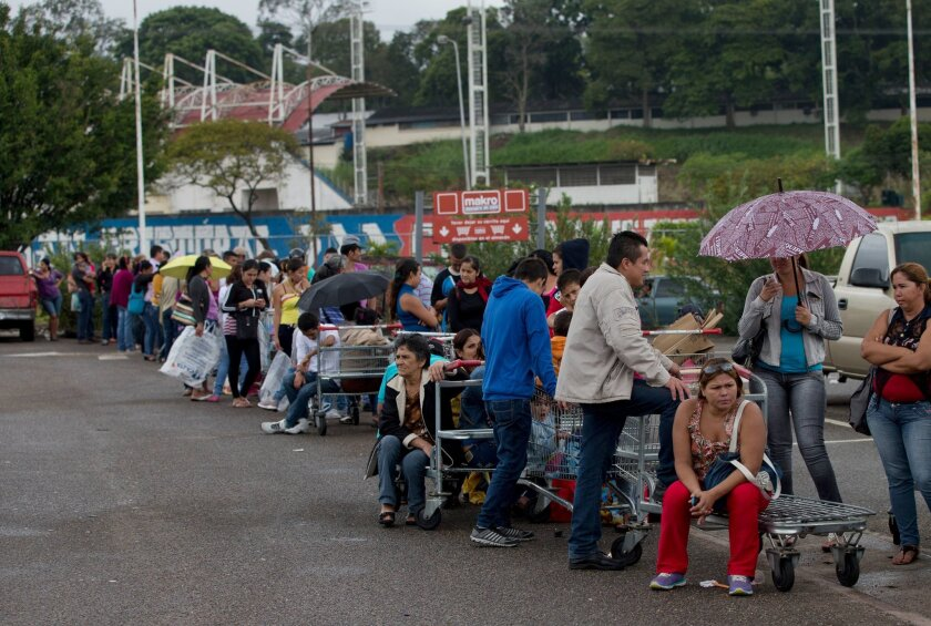 Venezuelans line up outside a supermarket in San Cristobal this week as the country faces a combination of shortages and spiraling inflation.