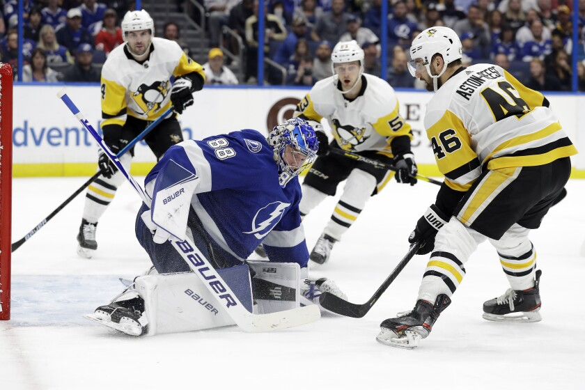 Tampa Bay Lightning goaltender Andrei Vasilevskiy (88) covers up after a shot by Pittsburgh Penguins center Zach Aston-Reese (46) during the third period of an NHL hockey game Thursday, Feb. 6, 2020, in Tampa, Fla. (AP Photo/Chris O'Meara)
