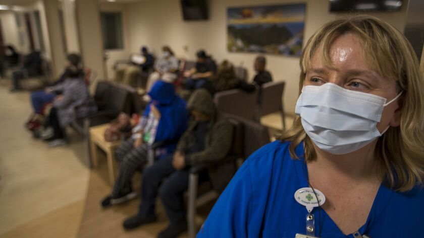 A charge nurse monitors patients in a hospital emergency room during flu season last January.