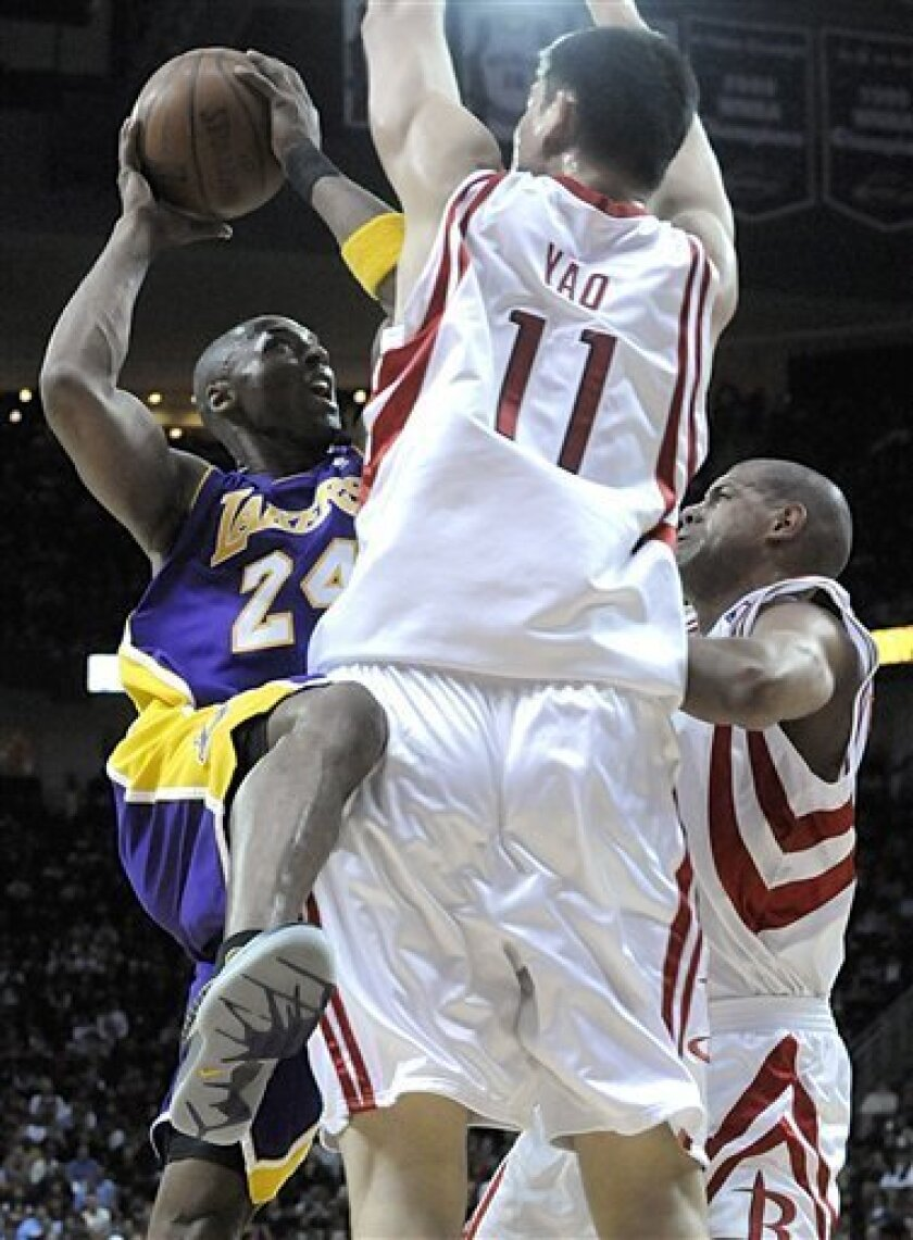 Los Angeles Lakers' Kobe Bryant (24) tries to shoot over Houston Rockets' Yao Ming (11), of China, and Shane Battier during the first half of an NBA basketball game Tuesday, Jan. 13, 2009, in Houston. Bryant had 33 points in the Lakers' 105-100 win. (AP Photo/Pat Sullivan)
