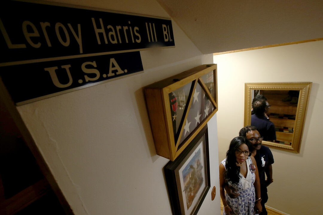 Guiselle and Leroy Harris Jr. have pictures, a flag and a sign honoring their son along their stairs