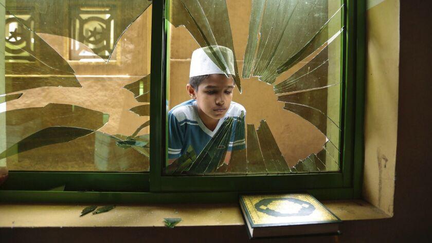 A Sri Lankan Muslim boy peeps through a broken window of a vandalized Mosque in Diana, Kandy, Sri La