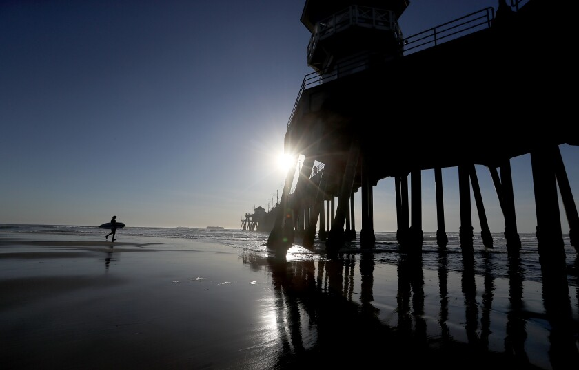 A surfer catches the last waves of the year in Huntington Beach on Dec. 31, 2020.
