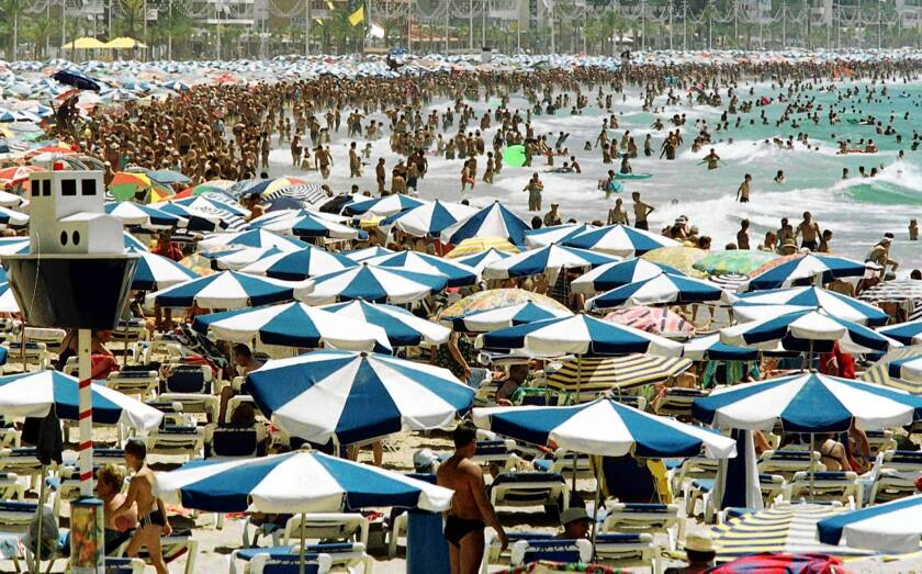 In Benidorm, Spain, bathers crowd a Mediterranean beach. With the nation's economy struggling, a beachfront apartment in the area may sell for as little as $130,000.