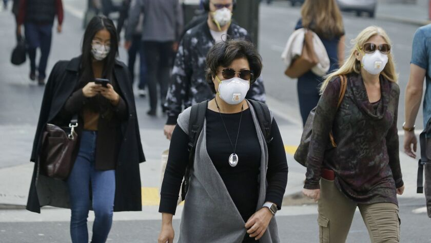 People wear masks while walking through the Financial District in the smoke-filled air Friday, Nov.