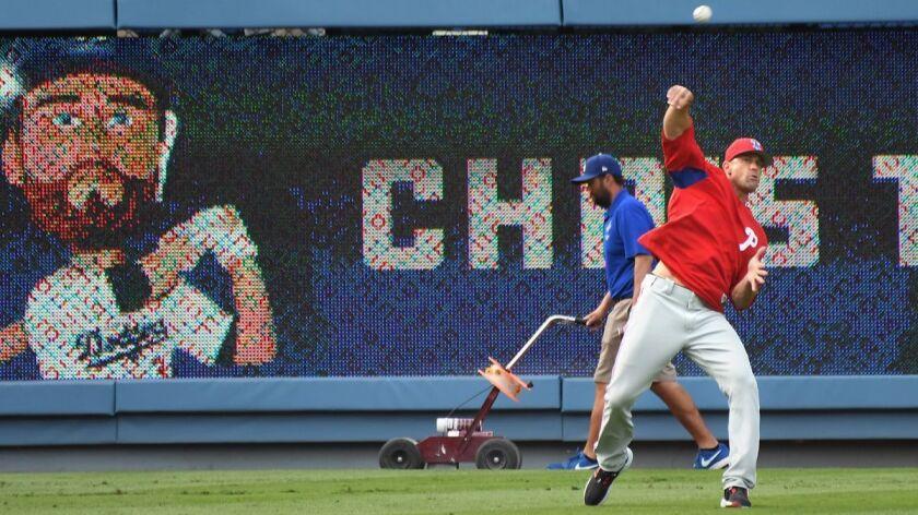 Philadelphia Phillies manager Gabe Kapler retrieves baseballs during batting practice before a game against the Dodgers at Dodger Stadium on Wednesday.