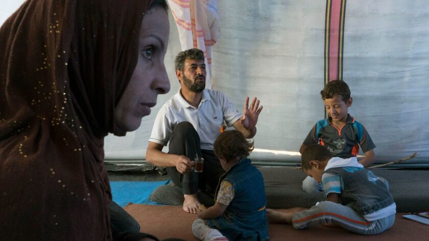 In this Wednesday, April 5, 2017 photo, Intisar Jadan Sultan, left, sits with her family in a tent a