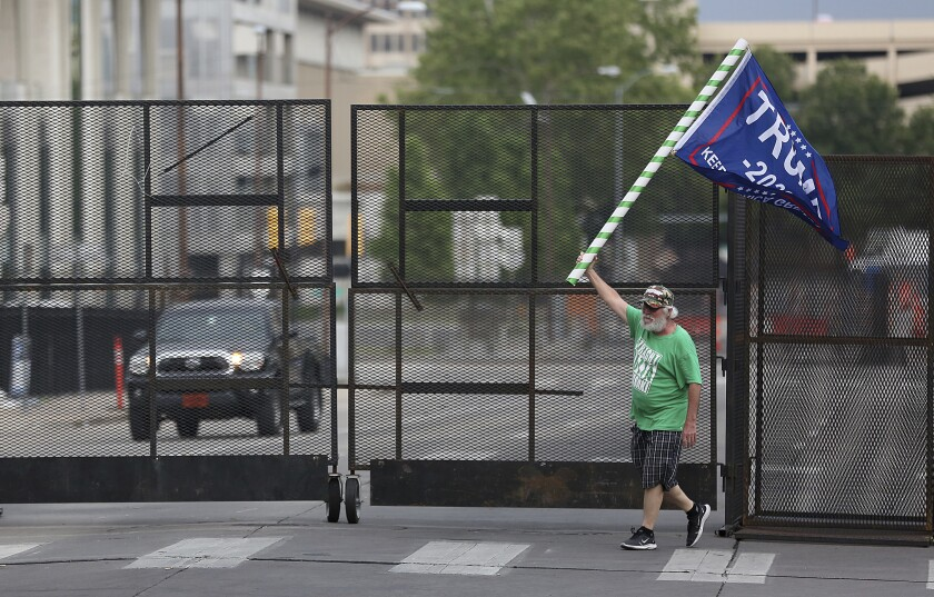 Mike Pellerin waves a Trump campaign flag in downtown Tulsa, Okla., ahead of the president's Saturday's campaign rally.