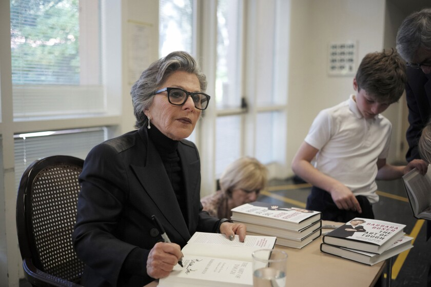 Former California Sen. Barbara Boxer, with grandson Zain, 9, signs books before giving a speech at UC Berkeley on Friday.