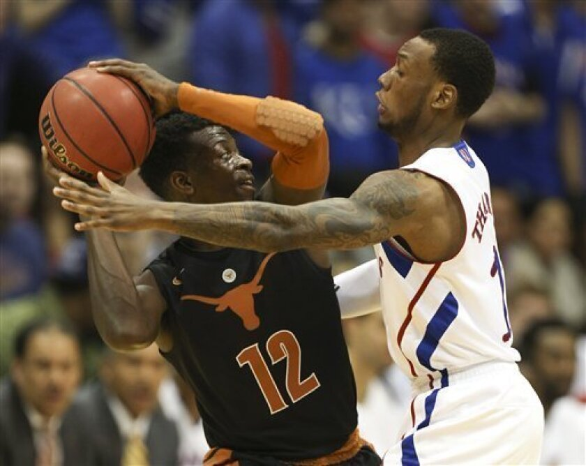 Texas guard Myck Kabongo (12) looks to pass around Kansas uard Naadir Tharpe during the first half of an NCAA college basketball game on Saturday, Feb. 16, 2013, in Lawrence, Kan. (AP Photo/Ed Zurga)