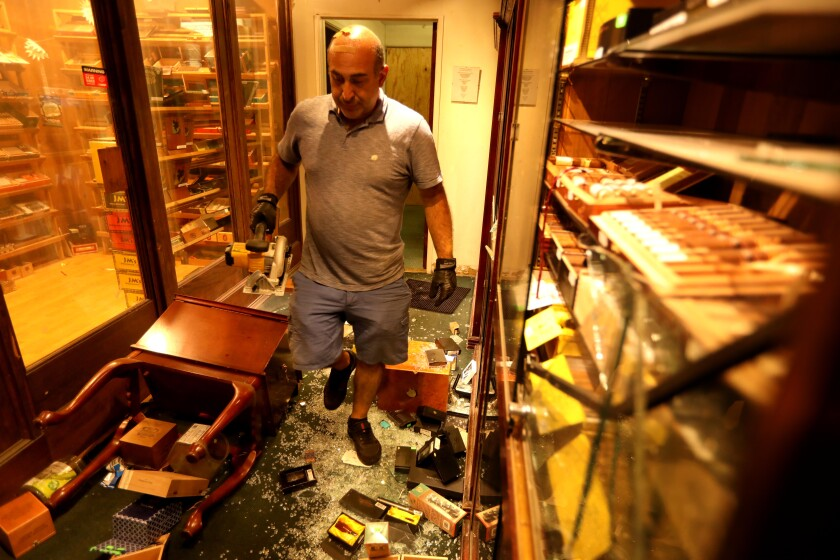 Santa Monica Tobacco owner Moe T. walks through his store Monday, the day after intruders smashed cases and stole items.