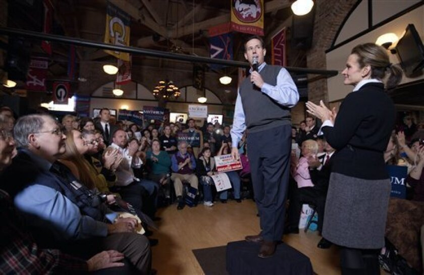 Republican presidential candidate former Pennsylvania Sen. Rick Santorum speaks at a campaign event as his wife Karen, right, listens Sunday, Jan. 8, 2012, in Greenville, S.C. (AP Photo/David Goldman)