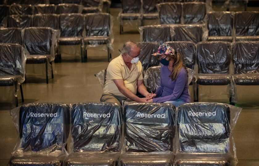A man and woman hold hands and pray among plastic-covered chairs in a church.