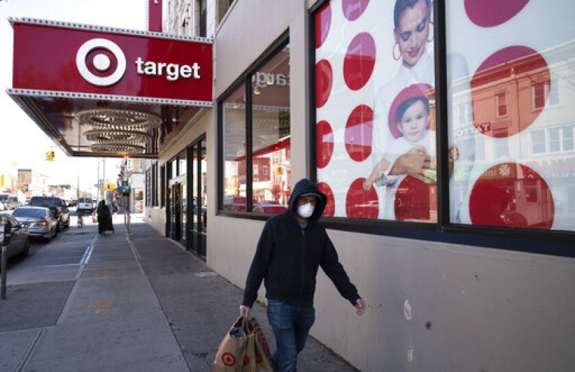 FILE - In this April 6, 2020 file photo, a customer wearing a mask carries his purchases as he leaves a Target store during the coronavirus pandemic in the Brooklyn borough of New York. Target has joined a growing list of major retailers that will require customers at all their stores to wear face coverings. The Minneapolis, Minnesota-based discounter said Thursday, July 16, that the policy will go into effect Aug. 1.(AP Photo/Mark Lennihan, File)
