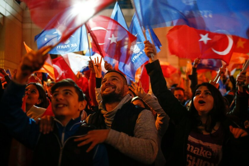 Supporters of Turkey's President Recep Tayyip Erdogan and The Justice and Development Party, (AKP), wave their party and national flags as they celebrates outside the AKP headquarters, in Istanbul, Sunday, Nov. 1, 2015.  Tens of millions of Turkish voters cast ballots in a contest that will determi