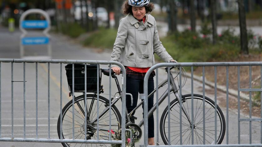 Celia Imrey pauses after laying flowers at the edge of a Manhattan bike path where eight people were killed on Tuesday.