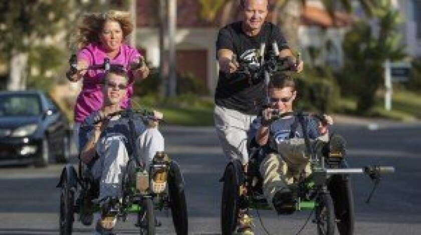 Jim and Lisa Pathman of Del Mar push their 16-year-old twin sons Shane, left, and Riley, who were born with cerebral palsy, as they demonstrate the racing chairs they planned to use Oct. 19 so that all four of them could compete in a triathlon.