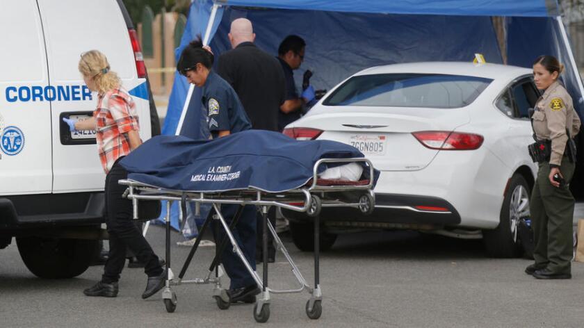 Funcionarios del forense del condado de Los Ángeles retiran el cuerpo de un hombre, hallado en un automóvil durante agosto pasado, en West 108th Street, en el área de Willowbrook (Mark Boster / Los Angeles Times).