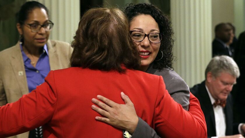 Assemblywoman Cristina Garcia (D-Bell Gardens), right, is hugged by Assemblywoman Eloise Reyes (D-Grand Terrace) on her first day back in the Assembly since an investigation into sexual misconduct charges.