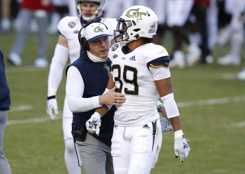 Georgia Tech head coach Geoff Collins talks to defensive back Wesley Walker (39) during an NCAA college football game against N.C. State in Raleigh, N.C., Saturday, Dec. 5, 2020. (Ethan Hyman/The News & Observer via AP, Pool)