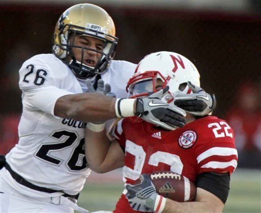 Colorado safety Ray Polk (26) commits a face mask penalty against Nebraska running back Rex Burkhead (22) during the first half of an NCAA college football game, in Lincoln, Neb., Friday, Nov. 26, 2010. (AP Photo/Nati Harnik)