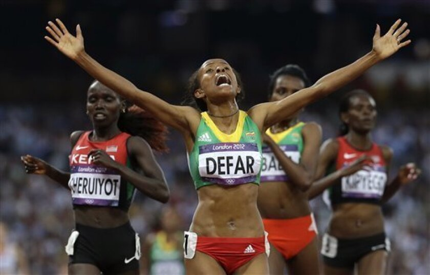 Ethiopia's Meseret Defar reacts as she crosses the finish line to win the 5000-meter final during the athletics in the Olympic Stadium at the 2012 Summer Olympics, London, Friday, Aug. 10, 2012. (AP Photo/Anja Niedringhaus)