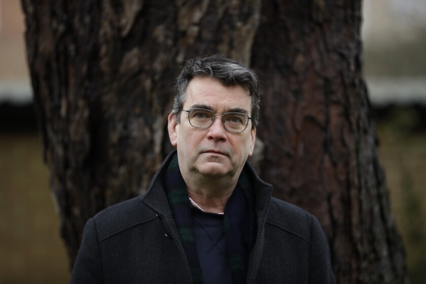 """British novelist Mick Herron, the author of the Slough House espionage series, poses for photographs outside his home in Oxford, England, Wednesday, Jan. 27, 2021. Like a spy in the night, writer Mick Herron's success has been stealthy. It took a while for the world to catch up with him. A decade after he introduced a crew of flawed secret agents caught between sinister plotters and cynical spymasters in the novel """"Slow Horses,"""" Herron is a best-selling thriller writer who has been likened to John le Carré and won a coveted Golden Dagger award from the Crime Writers' Association. The seventh novel in the series, """"Slough House,"""" is out in Feb. 2021, and a TV series is in production with an A-list cast led by Gary Oldman. But initially, few took notice. (AP Photo/Matt Dunham)"""