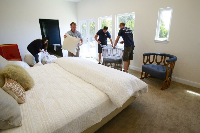 Silvera and Erin Eifler set up the bed in the master bedroom of the La Jolla home.