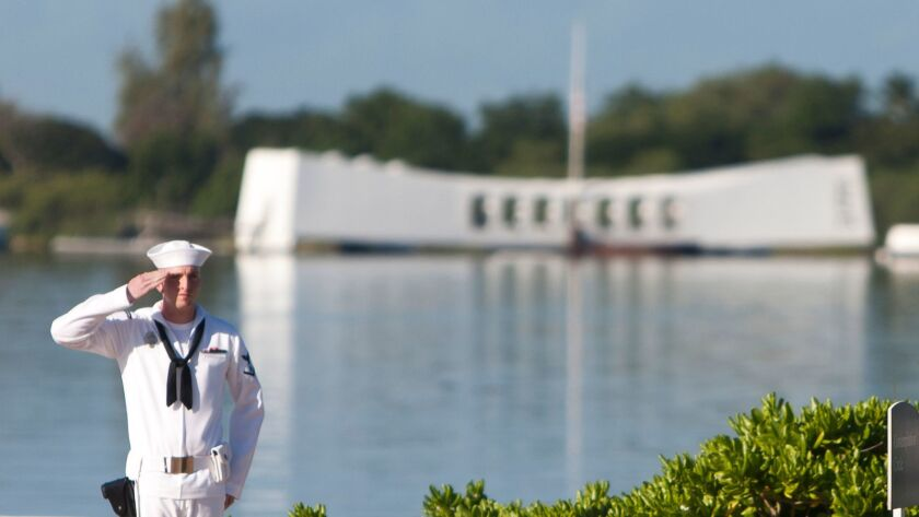 Navy rifleman standing at attention by the USS Arizona.