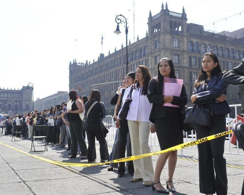 Imagen de personas desempleadas en espera de aplicar a un puesto en la Feria del Empleo que cada año se desarrolla en el zócalo de la capital de México. EFE/Archivo