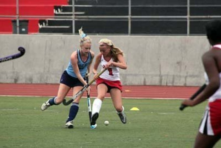Field hockey players go after the ball. Photo: Phil Dailey