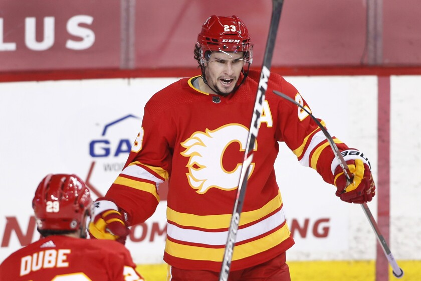 Calgary Flames' Sean Monahan, right, celebrates his goal against the Edmonton Oilers with Dillon Dube during the second period of an NHL hockey game Saturday, April 10, 2021, in Calgary, Alberta. (Larry MacDougal/The Canadian Press via AP)