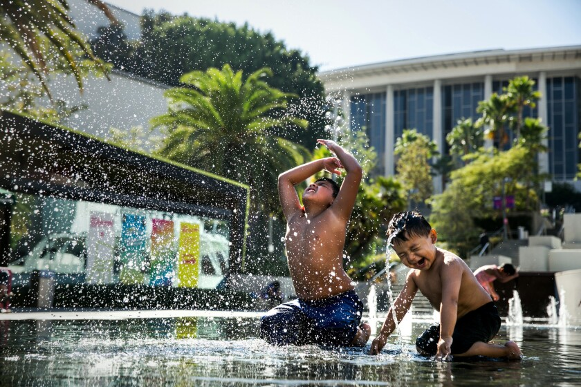 Nathan Gomez, 2, right, learns to mimic his older brother, Matthew Gomez, 9, left, as they use their heads to fling water in the air while playing at the water fountain at Grand Park.