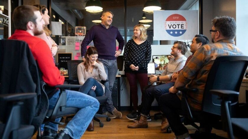 SRW agency founders Charlie Stone and Kate Weidner, center, explain to several employees they will have a paid day off on Election Day during a meeting, Oct. 25, 2018, in Chicago.