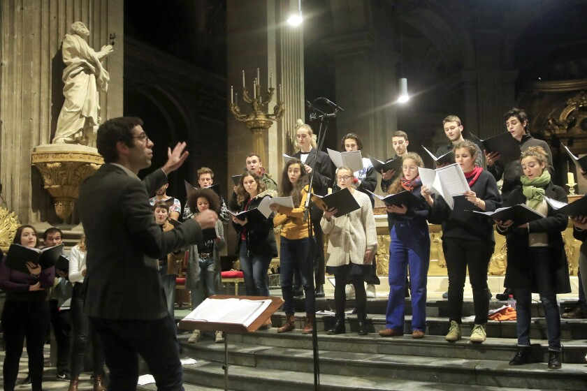 Henri Chalet directs the Notre Dame Cathedral's choir during a rehearsal at the St. Sulpice church in Paris on Monday, as the choir continues in other venues.