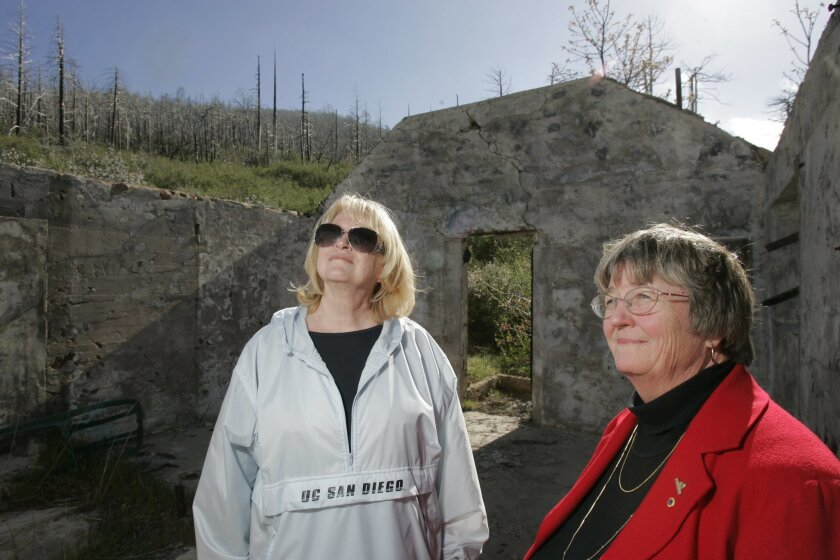 Camp Fire officials Lynne Cary (left) and Katie Zolezzi inspect the remains of a stone building last week at Camp Wolahi in the Cuyamacas. CHARLIE NEUMAN • U-T