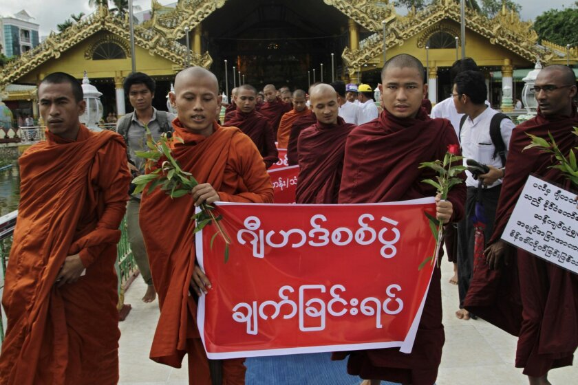 """Myanmar Buddhist monks march as they stage a rally against recent violence in central Myanmar, Friday, July 4, 2014, in Yangon, Myanmar. Myanmar's second-largest city is quiet Friday after an overnight curfew restored calm following two nights of violent rampages by extremist Buddhists. Authorities imposed the curfew in Mandalay late Thursday after attacks on minority Muslims left two people dead and 14 injured, raising fears that ethnic violence that has plagued the country for two years may escalate again. The banner reads """"Stop Jihad War.""""(AP Photo/Khin Maung Win)"""