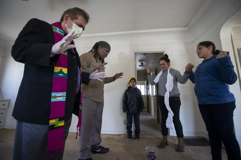 Protesters and their supporters pray inside of a home in El Sereno on Wednesday.