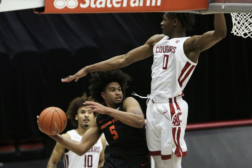 Oregon State guard Ethan Thompson (5) prepares to pass the ball past Washington State center Efe Abogidi (0) during the second half of an NCAA college basketball game in Pullman, Wash., Wednesday, Dec. 2, 2020. Washington State won 59-55. (AP Photo/Young Kwak)