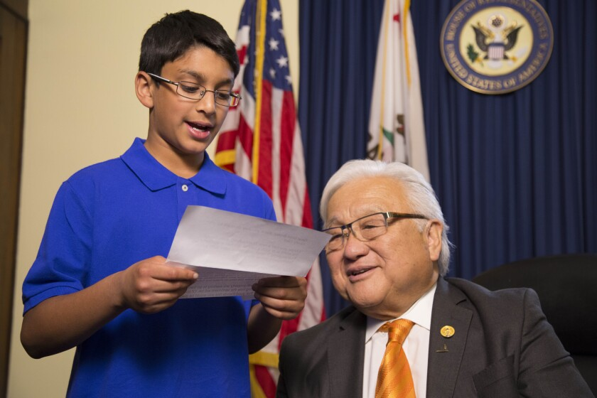 A Muslim American child reads a letter from a Japanese internment camp victim, with Rep. Mike Honda.