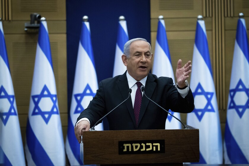 Israeli Prime Minister Benjamin Netanyahu stands at a lectern in front of Israeli flags.