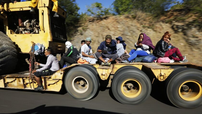 Migrants traveling with a caravan hoping to reach the U.S. border, ride on the bed of a truck, on th