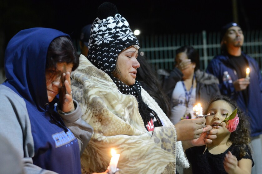 Dozens of people, including Annebell Flores (center) the mother of a 15-year-old girl shot at Balderrama Park in September, attended events in Oceanside to remember the victims of violence and mark the tenth anniversary of the shooting death of Police Officer Dan Bessant.