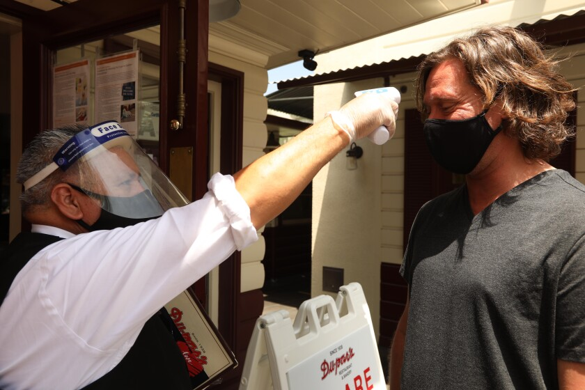 A waiter checks the temperature of a customer before allowing him to enter an L.A. restaurant.