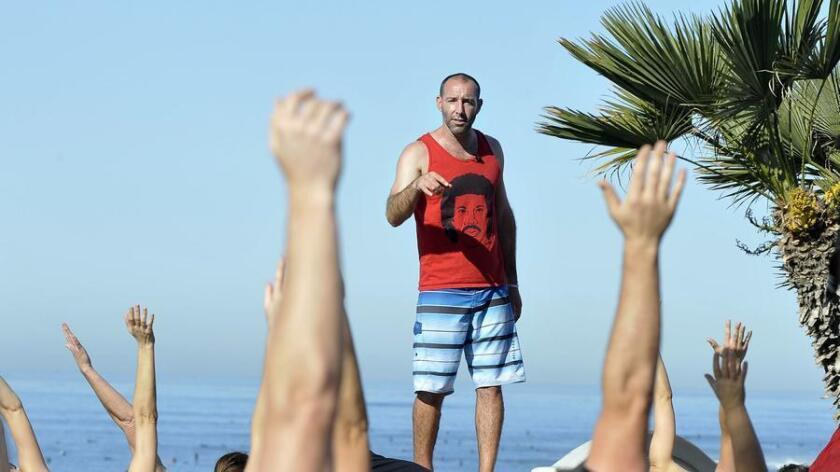 Steve Hubbard, aka NamaSteve, leads students into trikanasana (triangle pose) during his Oceanfront Yoga class, a donation-based, weekend class that brings in yogis from all over SD to practice together on the cliffs overlooking the PB shoreline between Law and Loring streets. (Rick Nocon)