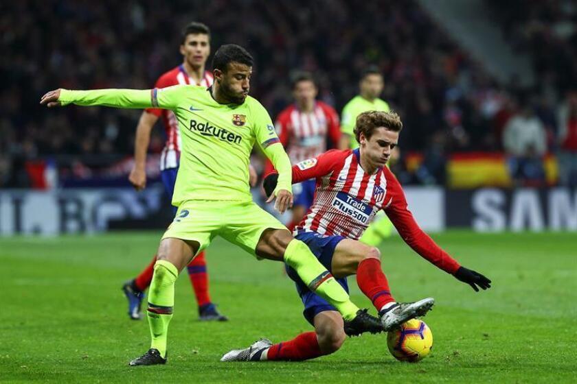 El delantero del Atlético de Madrid Griezmann (d) pelea un balón con Rafinha, del FC Barcelona, durante el partido de Liga en Primera División ante el FC Barcelona disputado anoche en el estadio Metropolitano, en Madrid. EFE