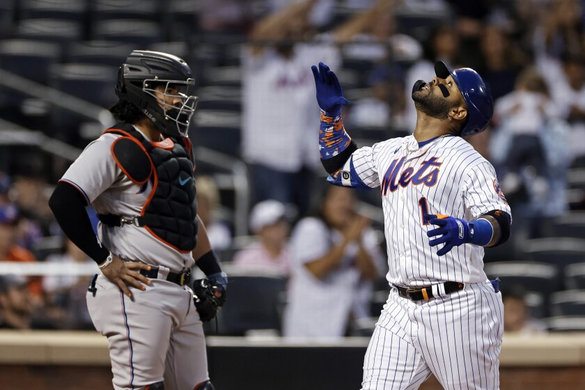 New York Mets' Jonathan Villar celebrates a home run in front of Miami Marlins catcher Jorge Alfaro during the first inning of a baseball game Thursday, Sept. 2, 2021, in New York. (AP Photo/Adam Hunger)