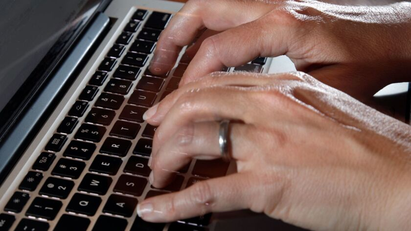 In this Monday, June 19, 2017, photo, a person types on a laptop keyboard, in North Andover, Mass. T